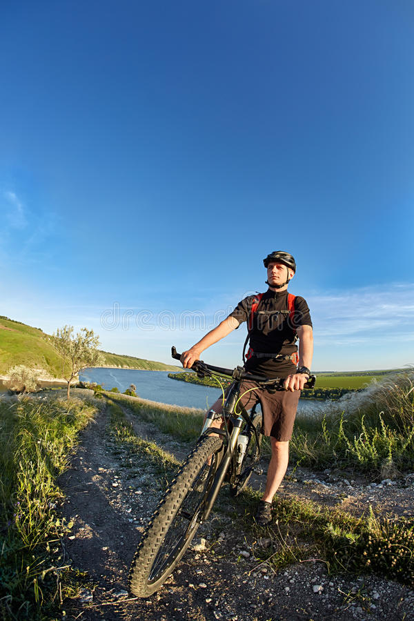 Ελκυστικός ποδηλάτης που στέκεται με το ποδήλατο και που παρατηρεί την άποψη ενάντια στο μπλε ουρανό στοκ εικόνες