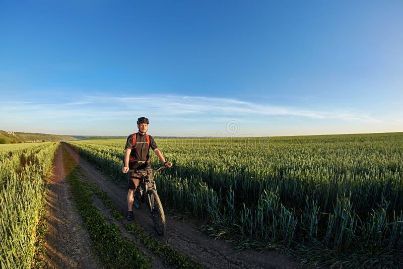 Ελκυστικός ποδηλάτης που στέκεται με το ποδήλατο και που παρατηρεί την άποψη ενάντια στο μπλε ουρανό στοκ φωτογραφίες