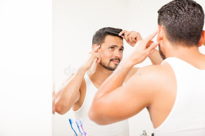 Ελκυστικός τύπος που κτενίζει την τρίχα του στο λουτρό στοκ φωτογραφία με δικαίωμα ελεύθερης χρήσης