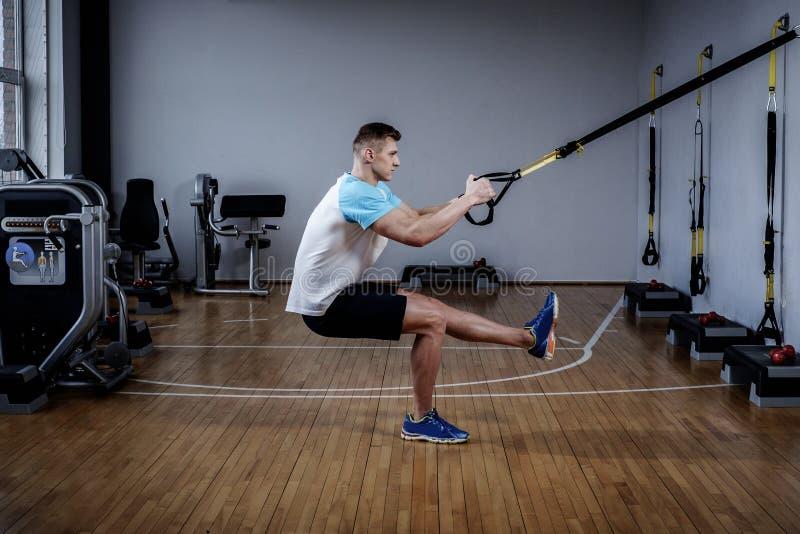 Ελκυστικό άτομο κατά τη διάρκεια του workout με τα λουριά αναστολής στη γυμναστική στοκ εικόνες με δικαίωμα ελεύθερης χρήσης