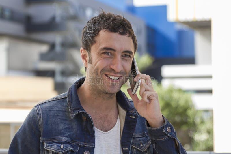 Ελκυστικό άτομο που μιλά στο κινητό τηλέφωνο στοκ εικόνα