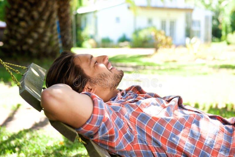Ελκυστικό άτομο που ξαπλώνει στην αιώρα στην πίσω αυλή στοκ φωτογραφία με δικαίωμα ελεύθερης χρήσης