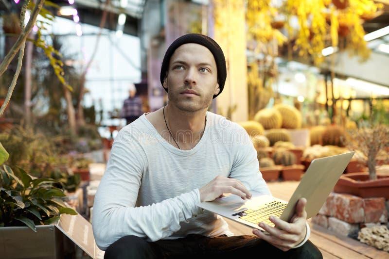 Ελκυστικό άτομο hipster που εργάζεται στο σύγχρονο φορητό προσωπικό υπολογιστή Κάθισμα σε πράσινο ηλιόλουστο ημερησίως πάρκων Ένν στοκ φωτογραφία