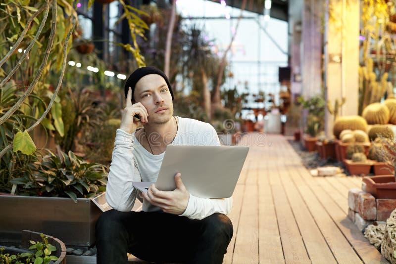 Ελκυστικό άτομο hipster που εργάζεται στο σύγχρονο φορητό προσωπικό υπολογιστή Κάθισμα σε πράσινο ηλιόλουστο ημερησίως πάρκων Ένν στοκ εικόνα με δικαίωμα ελεύθερης χρήσης