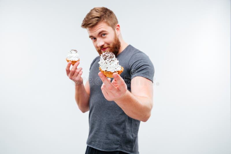 Ελκυστικό γενειοφόρο άτομο που παρουσιάζει κέικ κρέμας στοκ φωτογραφίες