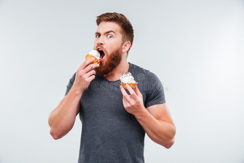 Ελκυστικό γενειοφόρο κέικ κρέμας δαγκώματος ατόμων στοκ εικόνα