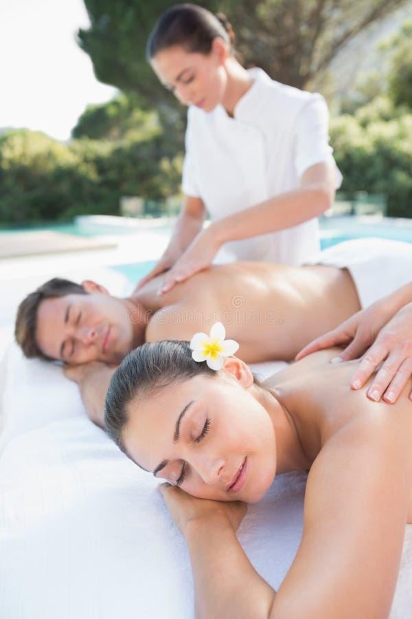 Ελκυστικό ζεύγος που απολαμβάνει το poolside μασάζ ζευγών στοκ εικόνα