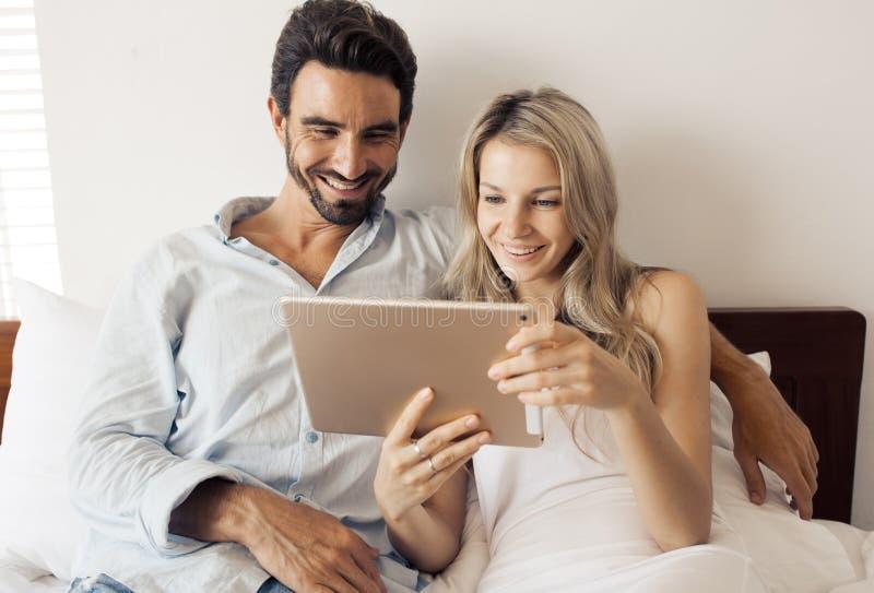 Ελκυστικό ζεύγος που χρησιμοποιεί την ταμπλέτα στην κρεβατοκάμαρα στοκ εικόνα με δικαίωμα ελεύθερης χρήσης