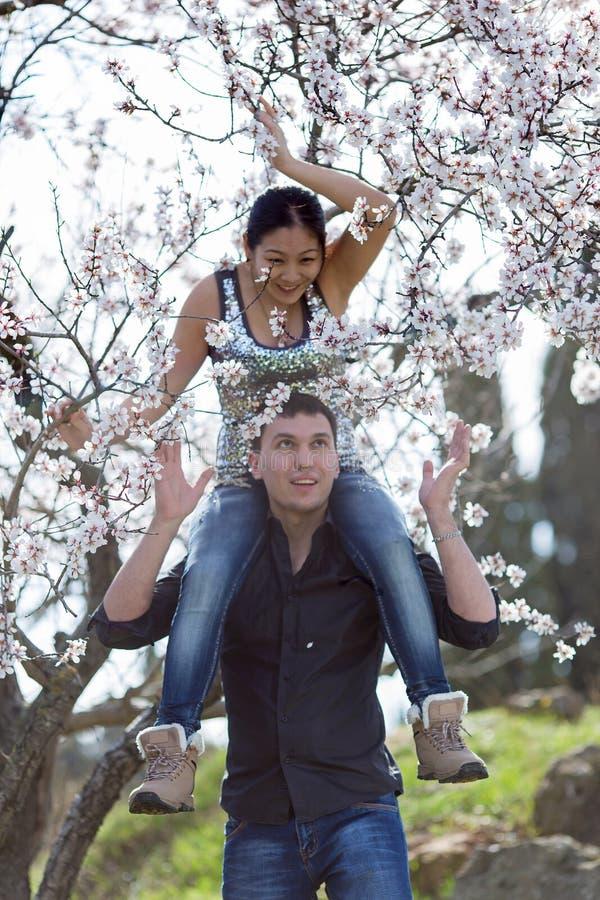 Ελκυστικό ζεύγος στο ανθίζοντας πάρκο, εστίαση στο πρώτο πλάνο στοκ φωτογραφίες