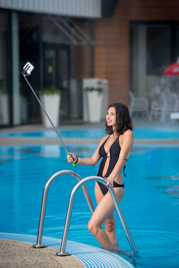 Ελκυστικό θηλυκό σε μια μαύρη τοποθέτηση μπικινιών ενάντια στην πισίνα, που παίρνει selfie τη φωτογραφία με το ραβδί selfie στο θ στοκ εικόνες