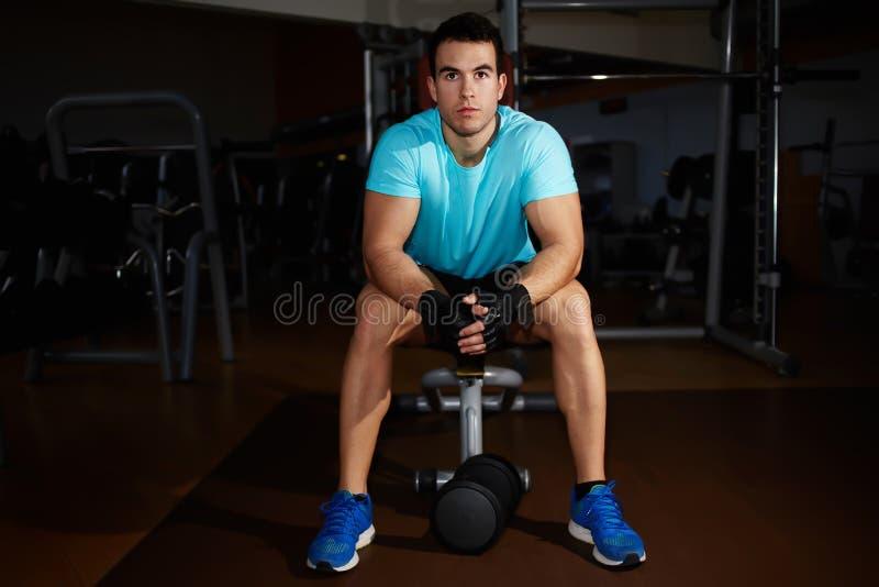 Ελκυστικό ισχυρό άτομο που παίρνει το σπάσιμο μετά από την κατάρτιση ικανότητας στη γυμναστική στοκ φωτογραφία με δικαίωμα ελεύθερης χρήσης