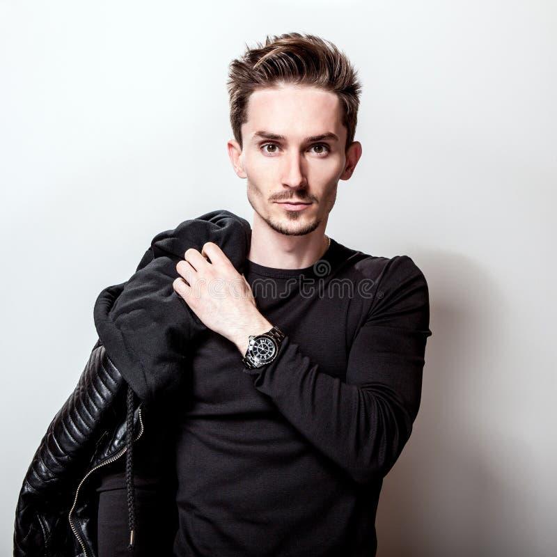Ελκυστικό κομψό άτομο στη μοντέρνη μαύρη τοποθέτηση σακακιών δέρματος στο ανοικτό γκρι υπόβαθρο στοκ εικόνες