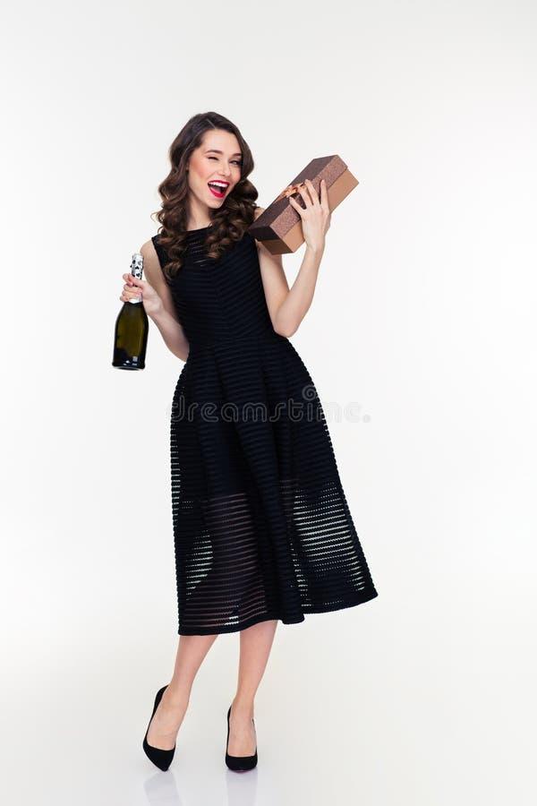 Ελκυστικό μπουκάλι εκμετάλλευσης γυναικών κλεισίματος του ματιού της σαμπάνιας και του δώρου στοκ εικόνα