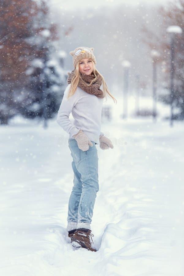 Ελκυστικό νέο ξανθό κορίτσι που περπατά στη χειμερινή δασική όμορφη γυναίκα στο wintertime υπαίθριο Φθορά των χειμερινών ενδυμάτω στοκ φωτογραφία