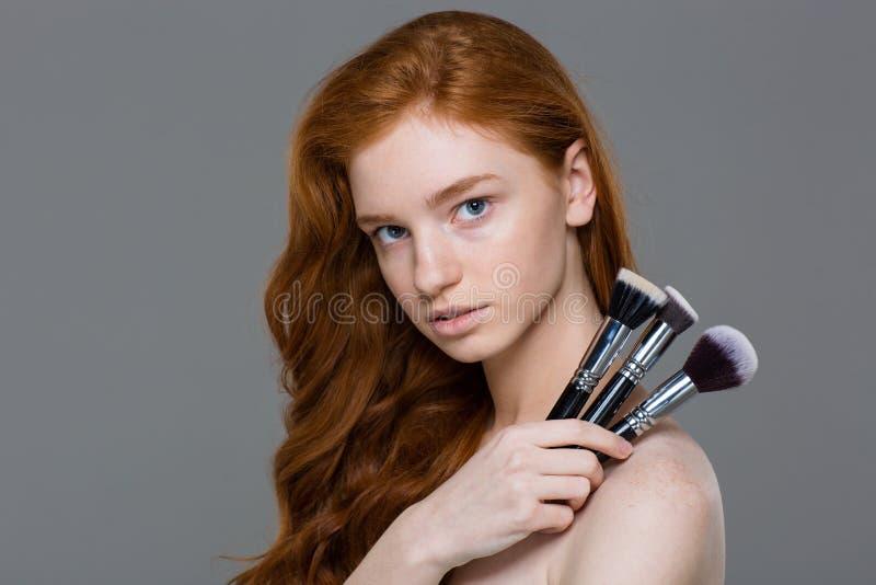 Ελκυστικό νέο redhead σύνολο εκμετάλλευσης γυναικών βουρτσών makeup στοκ φωτογραφίες