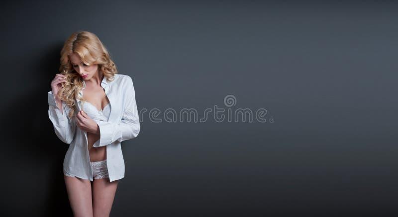 Ελκυστικό ξανθό πρότυπο με τον άσπρους στηθόδεσμο, το πουκάμισο και τα σορτς που στέκονται στο γκρίζο υπόβαθρο. Πορτρέτο μόδας ενό στοκ εικόνες