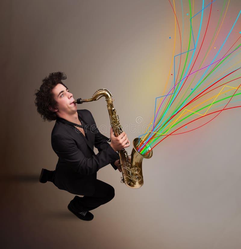 Ελκυστικό παιχνίδι μουσικών στο saxophone ενώ ζωηρόχρωμη περίληψη στοκ φωτογραφία