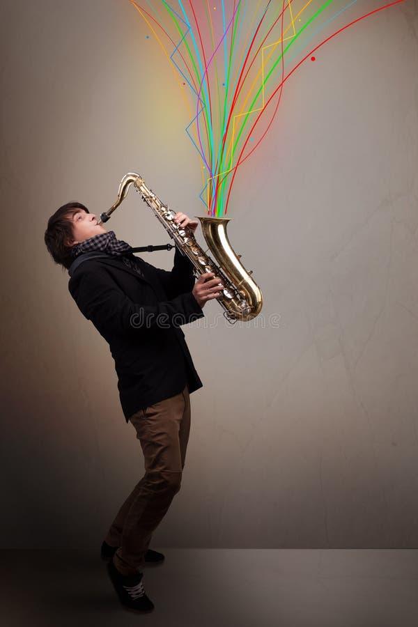 Ελκυστικό παιχνίδι μουσικών στο saxophone ενώ ζωηρόχρωμη περίληψη στοκ εικόνα