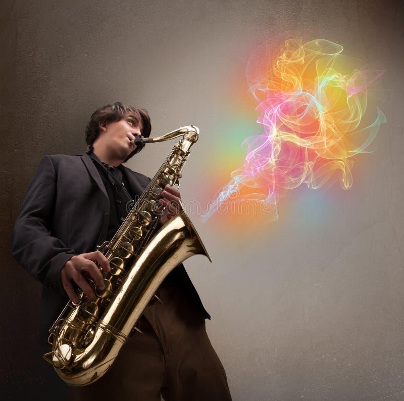 Ελκυστικό παιχνίδι μουσικών στο saxophone με τη ζωηρόχρωμη περίληψη στοκ εικόνα