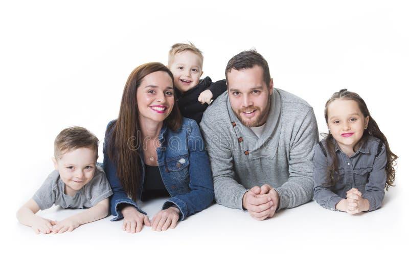 Ελκυστικό πορτρέτο της νέας ευτυχούς οικογένειας πέρα από το άσπρο υπόβαθρο στοκ εικόνα