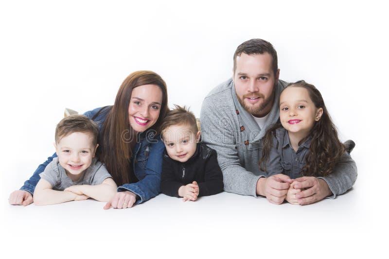 Ελκυστικό πορτρέτο της νέας ευτυχούς οικογένειας πέρα από το άσπρο υπόβαθρο στοκ φωτογραφία με δικαίωμα ελεύθερης χρήσης