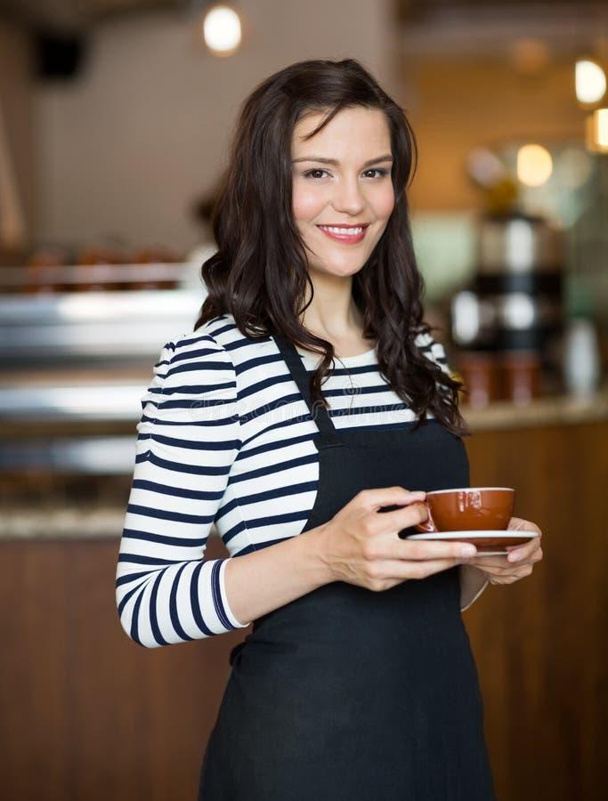 Ελκυστικό φλυτζάνι καφέ εκμετάλλευσης σερβιτορών μέσα στοκ φωτογραφία