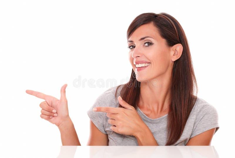 Ελκυστικό brunette που δείχνει το δικαίωμά της στοκ εικόνα