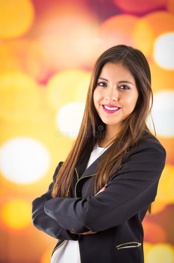 Ελκυστικό brunette που φορά το μαύρο σακάκι που θέτει φυσικά και που χαμογελά όμορφο στη κάμερα με μουτζουρωμένο ζωηρόχρωμο στοκ φωτογραφία με δικαίωμα ελεύθερης χρήσης