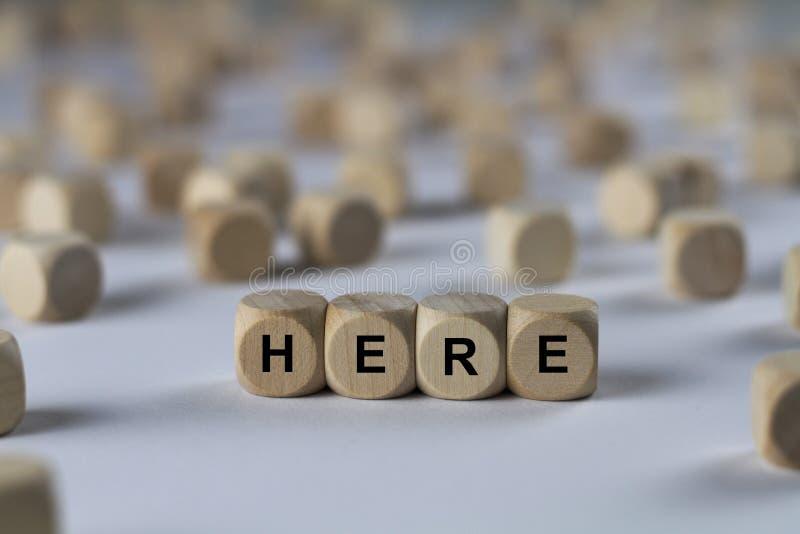 Εδώ - κύβος με τις επιστολές, σημάδι με τους ξύλινους κύβους στοκ εικόνα
