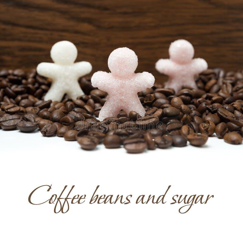 Ζάχαρη μικρών ατόμων στα φασόλια καφέ, που απομονώνονται υπό μορφή στοκ φωτογραφίες με δικαίωμα ελεύθερης χρήσης