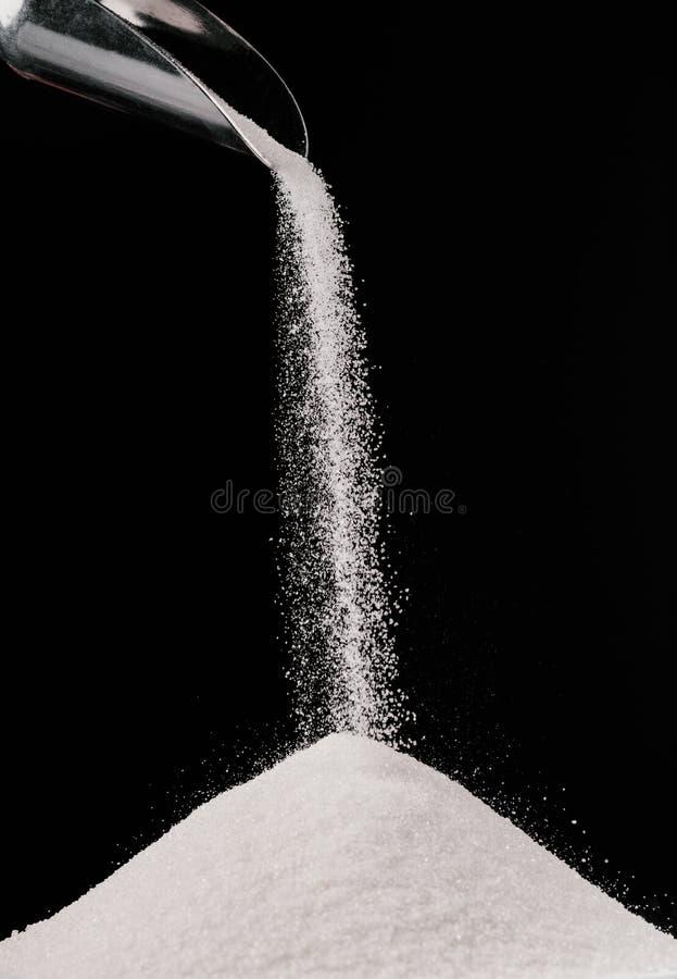 ζάχαρη που πέφτει από τη σέσουλα μετάλλων στο σωρό στοκ φωτογραφία
