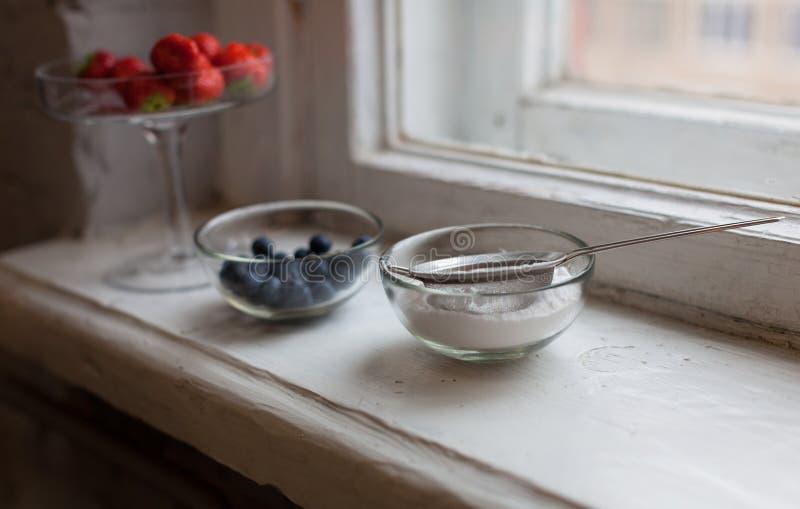 Ζάχαρη τήξης φραουλών βακκινίων σε ένα μικρό κύπελλο στο παράθυρο στοκ φωτογραφίες