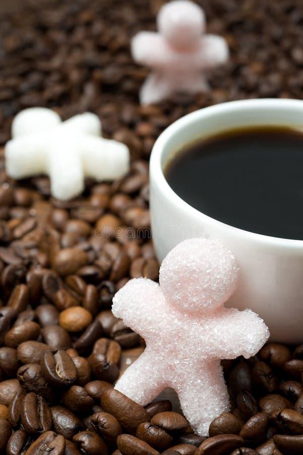 Ζάχαρη υπό μορφή μικρού ατόμου και φλιτζανιού του καφέ, κάθετων στοκ εικόνα με δικαίωμα ελεύθερης χρήσης