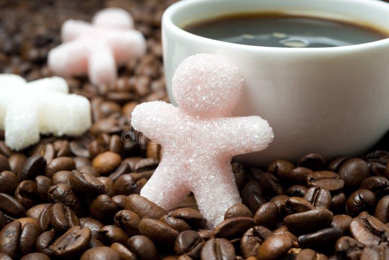 Ζάχαρη υπό μορφή μικρού ατόμου και φλιτζανιού του καφέ, κινηματογράφηση σε πρώτο πλάνο στοκ εικόνες
