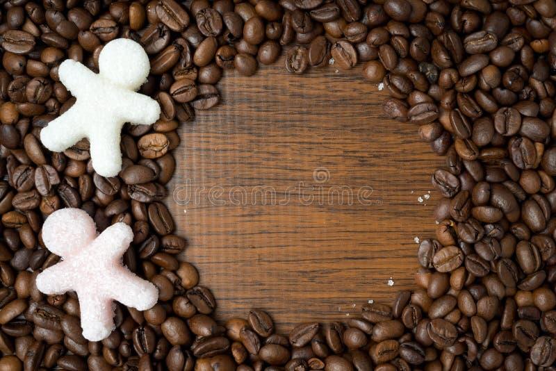 Ζάχαρη υπό μορφή μικρών ατόμων στα φασόλια καφέ, διάστημα για το κείμενο στοκ εικόνα με δικαίωμα ελεύθερης χρήσης