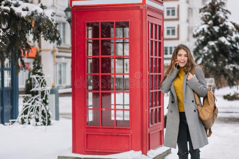 Ζαλίζοντας γυναίκα brunette στην κίτρινη ζακέτα που στέκεται κοντά στο βρετανικό κλήση-κιβώτιο στη χειμερινή ημέρα Υπαίθρια φωτογ στοκ φωτογραφία