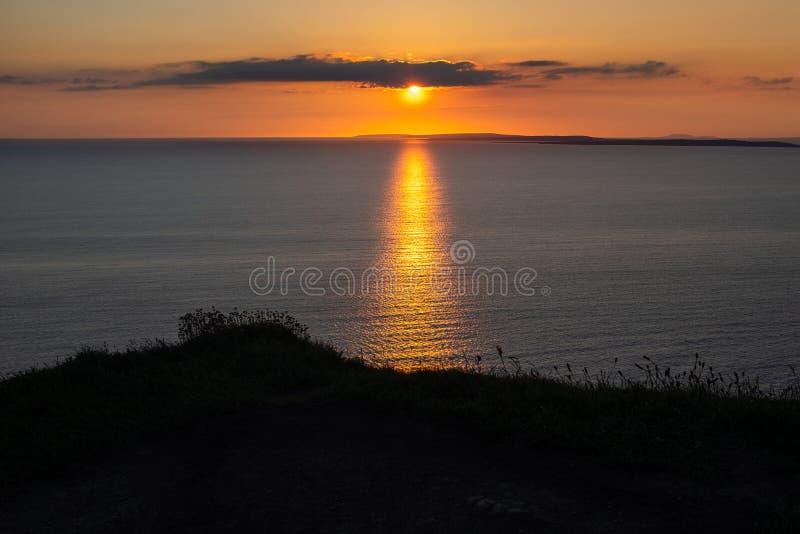Ζαλίζοντας χρυσό ηλιοβασίλεμα από τους απότομους βράχους Moher που κοιτάζει έξω προς το νησί Inisheer, Ιρλανδία στοκ εικόνα