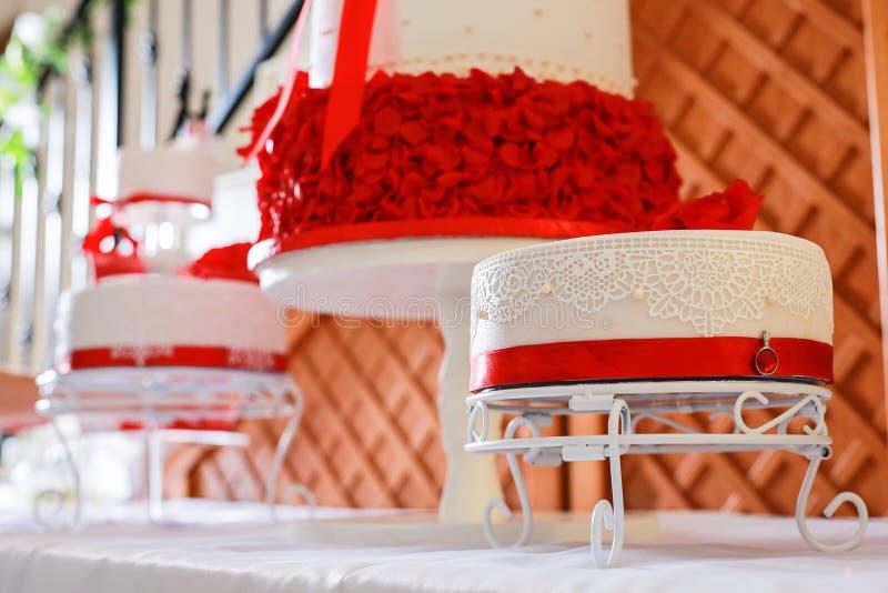 Ζαχαροπλάστης που διακοσμεί ένα γαμήλιο κέικ με τα λουλούδια αμυγδαλωτού στοκ εικόνα