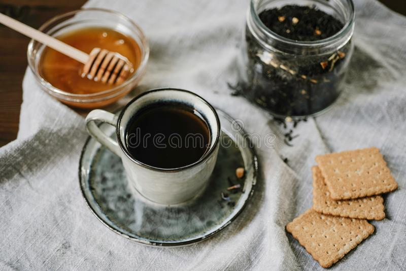 Ζεστά ποτό και γλυκά Φλυτζάνι, μέλι, μπισκότα και φύλλα τσαγιού άνω του τ στοκ φωτογραφίες με δικαίωμα ελεύθερης χρήσης