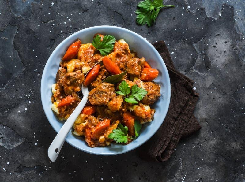 Ζεστή άνεση χειμερινό φθινοπωρινό φαγητό - πικάντικο βοδινό κρέας με πατάτες σε σκούρο φόντο, με κορυφαία θέα στοκ φωτογραφία