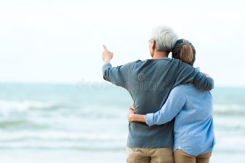 Ζευγάρι ηλικιωμένων της Asia Lifestyle αγκαλιάζει στην παραλία χαρούμενοι στον ρομαντικό έρωτα και στον χαλαρό χρόνο  Τουρισμός στοκ εικόνες με δικαίωμα ελεύθερης χρήσης