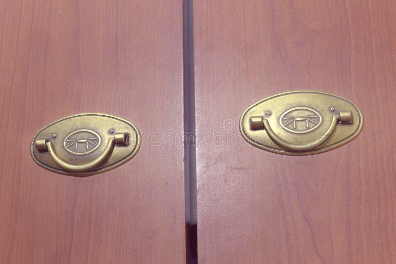 Ζευγάρι του ορείχαλκου που διπλώνει τις λαβές τραβήγματος στις ξύλινες πόρτες της ντουλάπας στοκ εικόνες