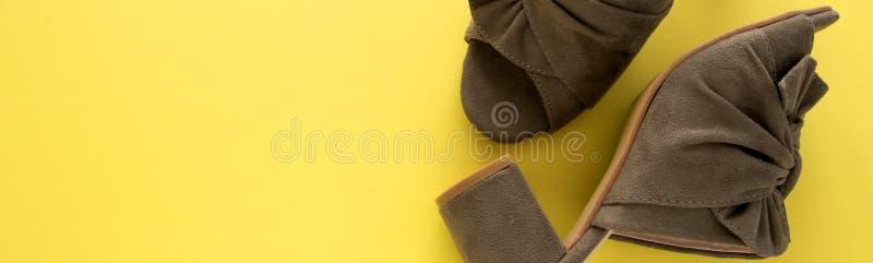 Ζευγάρι του στρατιωτικού πράσινου χρώματος μουλαριών/clogs στο φρέσκο κίτρινο υπόβαθρο στοκ εικόνες