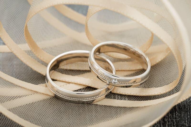 Ζευγάρι των απλών άσπρων χρυσών δαχτυλιδιών ζωνών στο μπεζ υπόβαθρο κορδελλών στοκ εικόνες με δικαίωμα ελεύθερης χρήσης
