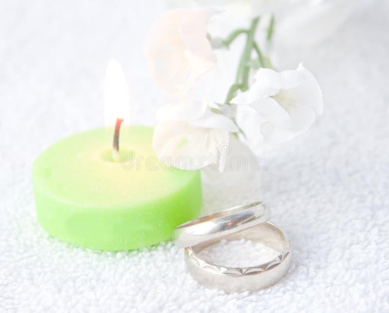 Ζευγάρι των γαμήλιων δαχτυλιδιών με το πράσινο κερί LIT στοκ φωτογραφία με δικαίωμα ελεύθερης χρήσης