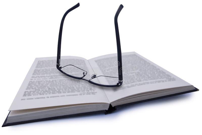 Ζευγάρι των θεαμάτων, που στηρίζεται στο βιβλίο με το μουτζουρωμένο κείμενο με το σαφές γράψιμο μέσω του φακού στοκ εικόνα με δικαίωμα ελεύθερης χρήσης