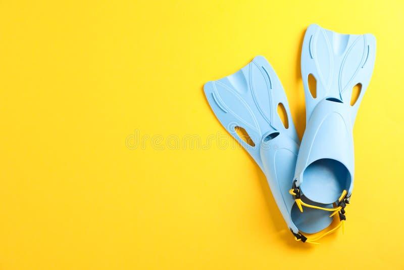 Ζευγάρι των μπλε βατραχοπέδιλων στο κίτρινο υπόβαθρο στοκ εικόνες