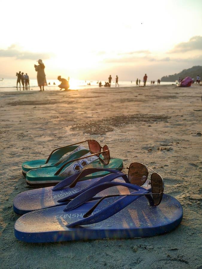 Ζευγάρι των παντοφλών με τις σκιές που τοποθετούνται σε τους σε μια παραλία στοκ φωτογραφία
