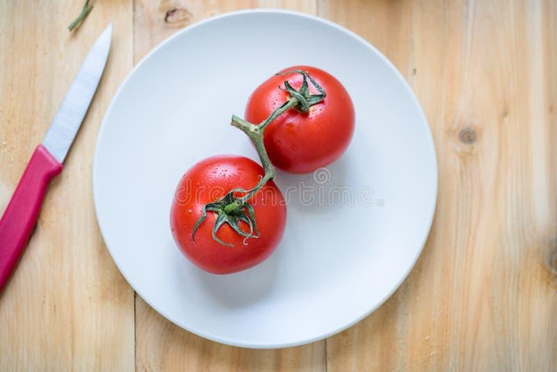 Ζευγάρι των φρέσκων κόκκινων ντοματών σε ένα άσπρο πιάτο στοκ εικόνα