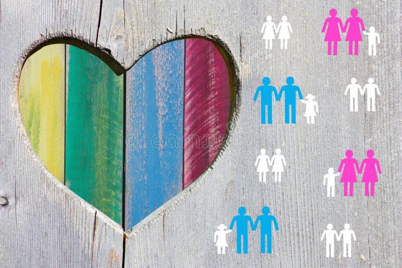 Ζεύγη και οικογένειες ομοφυλόφιλων και λεσβιών στο ξύλινο υπόβαθρο με την πολύχρωμη καρδιά ουράνιων τόξων στοκ φωτογραφία με δικαίωμα ελεύθερης χρήσης